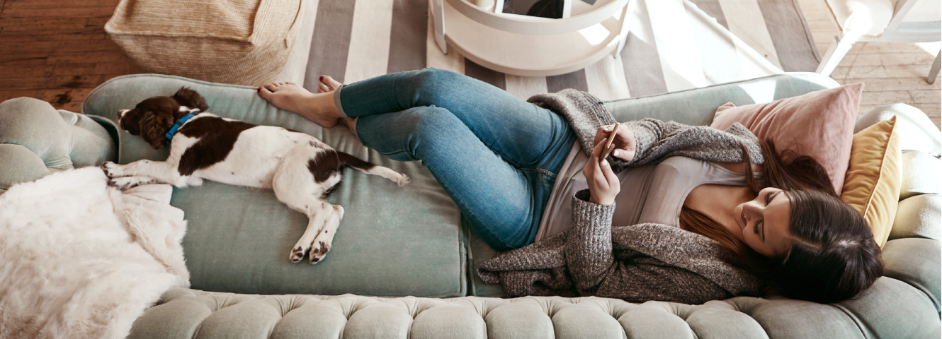 woman and her dog laying on couch